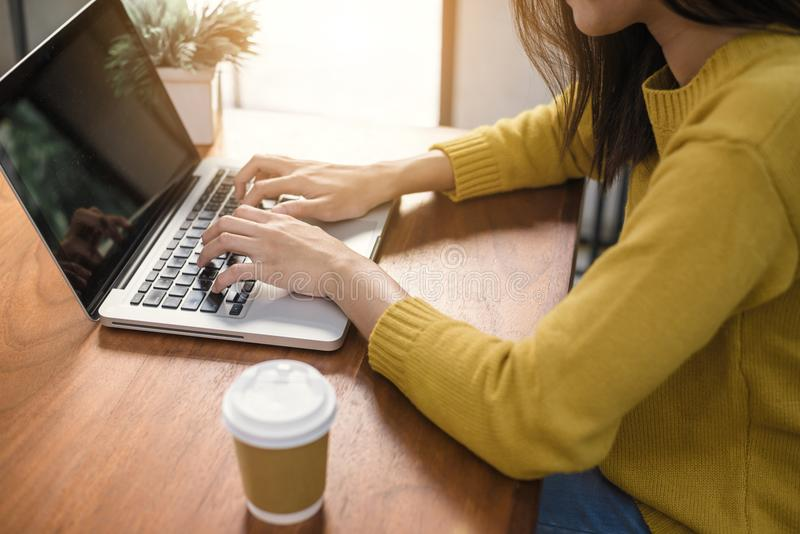 运作在办公室外的数字式生活方式 妇女递有黑屏的键入的便携式计算机在咖啡店的桌上 免版税库存图片