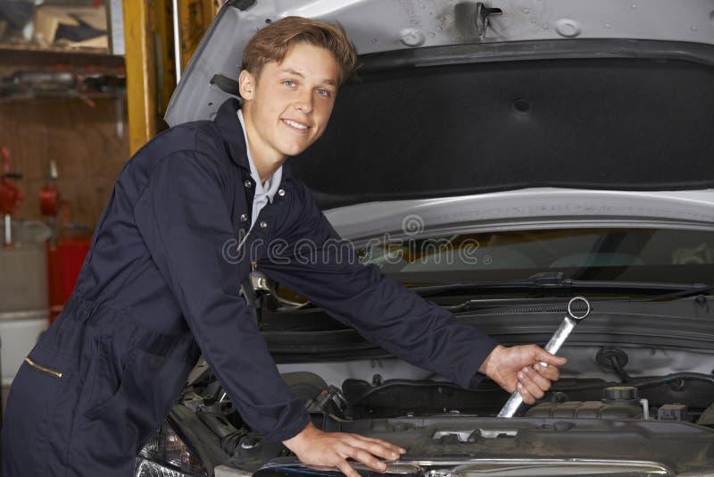 运作在发动机的汽车修理店的学徒技工 免版税库存照片