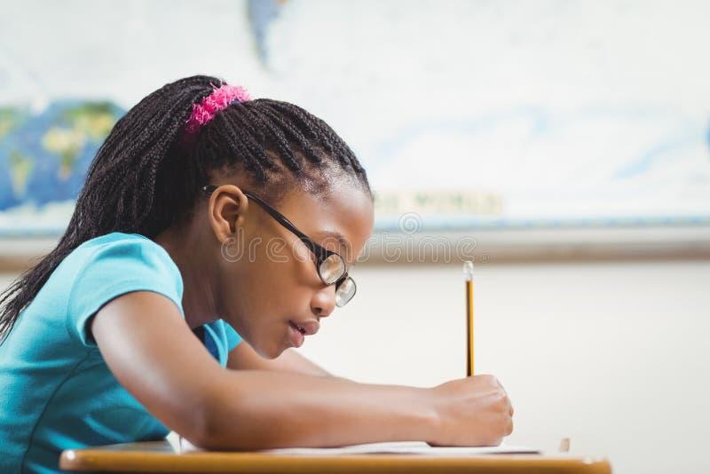 运作在她的书桌的被聚焦的学生在教室 库存图片
