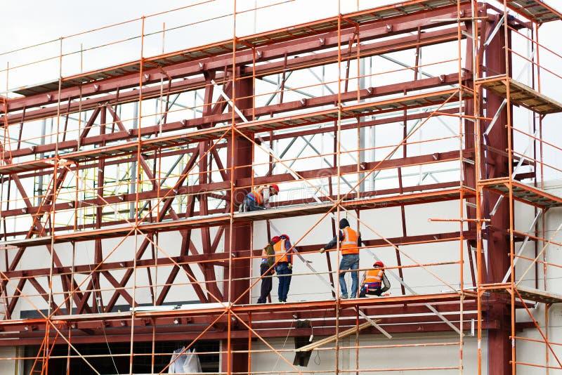 运作在建造场所的屋顶结构的工作者建造者 大厦队 免版税库存照片