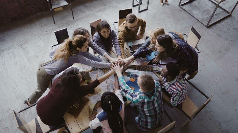 运作在时髦顶楼办公室的企业队顶视图 年轻混合的族种人在中心上一起把棕榈放 免版税图库摄影