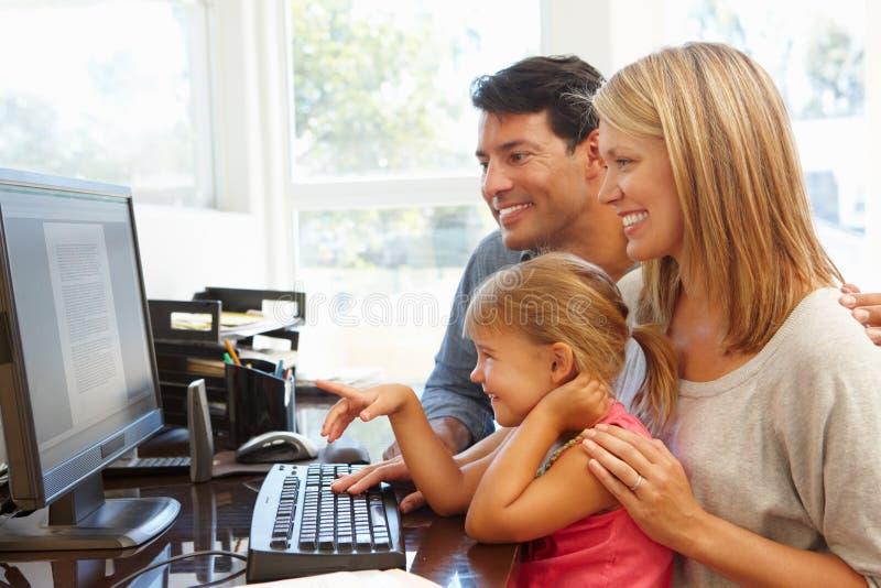 运作在有女儿的家庭办公室的夫妇 图库摄影