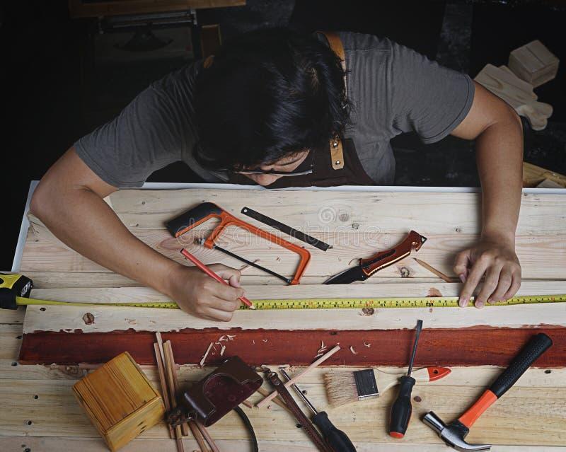 运作在木材加工车间的亚裔木匠顶视图 Mak 免版税库存照片