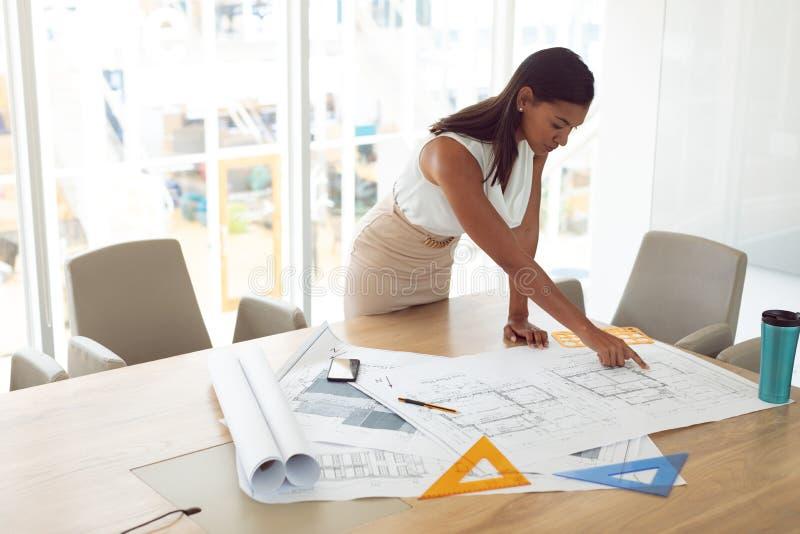 运作在桌上的图纸的女性建筑学在一个现代办公室 免版税库存图片