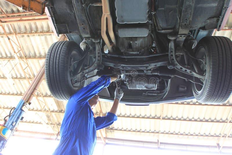 运作在汽车下的汽车修理师特写镜头在自动修理服务中 免版税库存图片