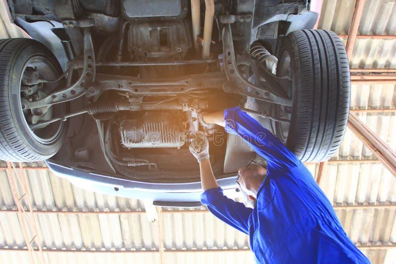 运作在汽车下的汽车修理师特写镜头在自动修理服务中 图库摄影