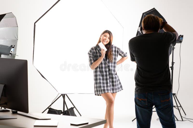 运作在现代照明设备演播室的摄影师和俏丽的模型 免版税图库摄影