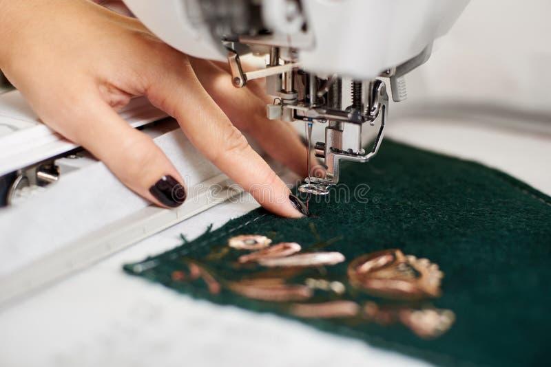 运作在缝纫机的妇女手特写镜头创造在纺织品细节的五颜六色的花卉样式 库存图片