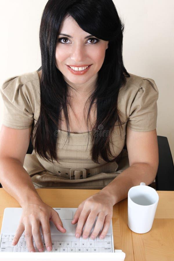 运作在膝上型计算机的书桌的妇女特写镜头 免版税库存图片
