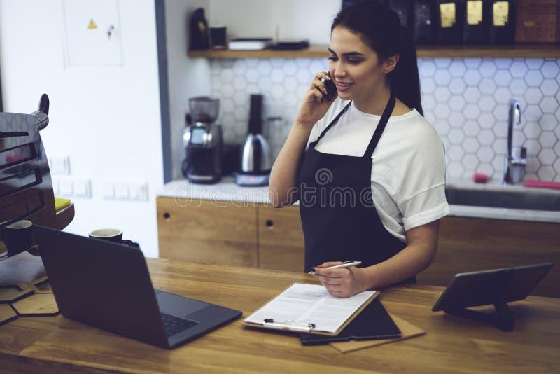运作在自助食堂的有吸引力的女性barista画象  库存照片