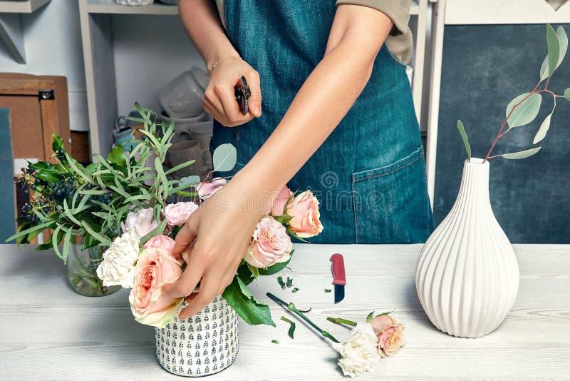 运作在花店的工作服的年轻女性 安排花束的卖花人的播种的图象 图象为,花交付 免版税库存照片