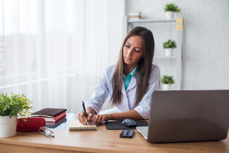 运作在医疗办公室工作场所文字处方的医师医生画象坐在书桌 库存图片