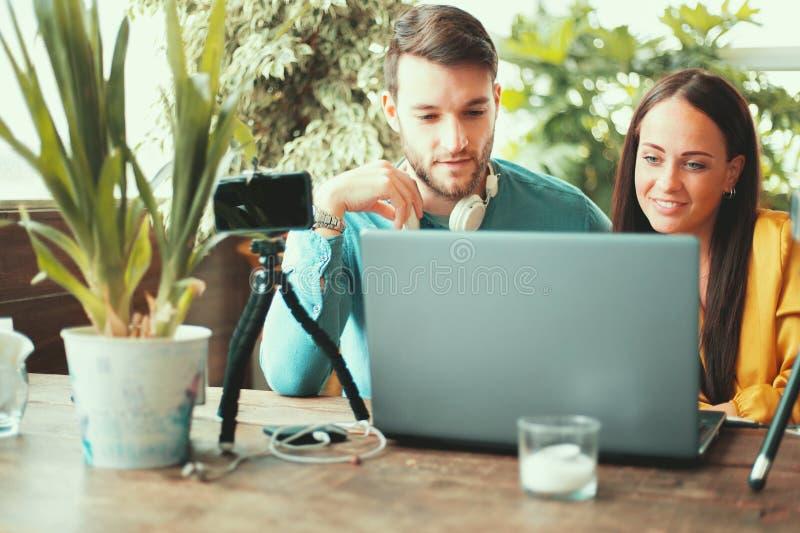 运作年轻夫妇的Co使用膝上型计算机,在三脚架的智能手机,坐在一起写博克桌的录影 免版税图库摄影