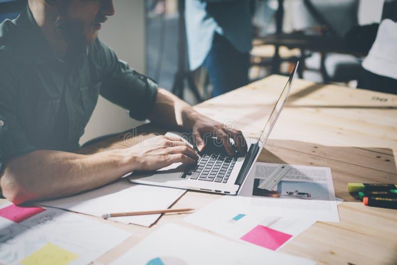 运作新的项目的有胡子的desugner内部 在木桌上的普通设计笔记本 分析计划手,键盘 免版税库存照片