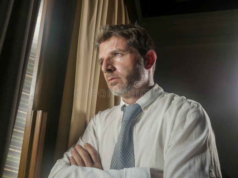 运作晚看的商人办公室画象通过周道的窗口和沮丧沉思的感觉担心哀伤和 免版税库存照片