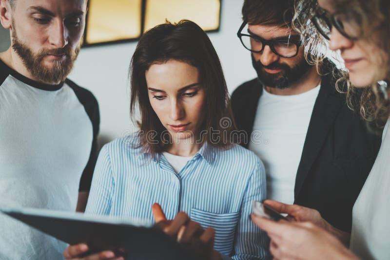 运作的片刻照片 一起使用电子触摸板的小组年轻工友在现代办公室顶楼 免版税库存照片