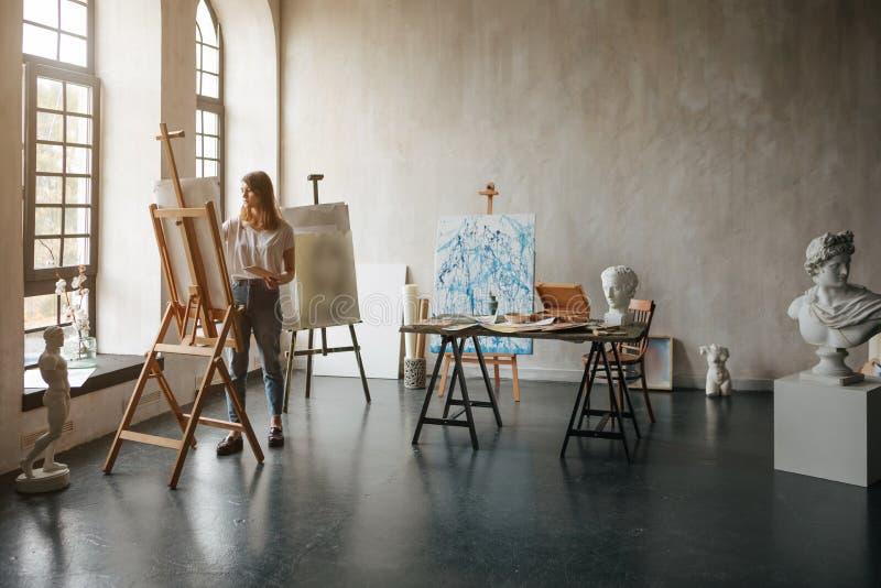 运作的过程的艺术家 创造绘画的年轻女人 有轻和古典雕塑胸象的车间室 免版税库存图片