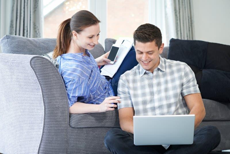 运作从家的自由职业者的夫妇一起看膝上型计算机 库存照片