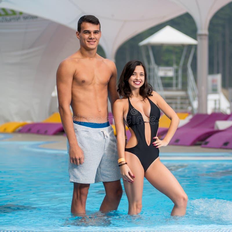 运动人和女孩有一个完善的图的在游泳池附近在豪华山区度假村有被弄脏的背景 库存照片