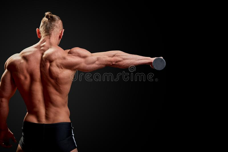 运动人摆在 人照片有完善的体质的在黑背景 r 力量和刺激 免版税库存照片