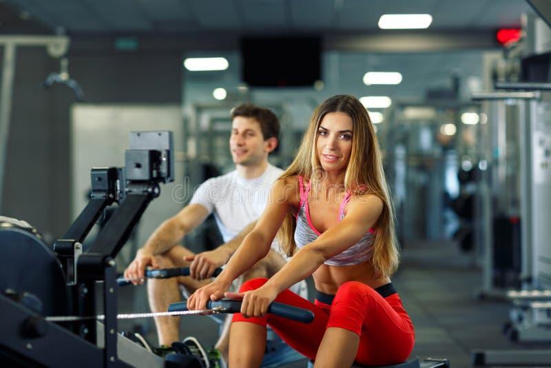 运动做在划船模拟器的男人和妇女锻炼在阴级射线示波器 免版税库存照片