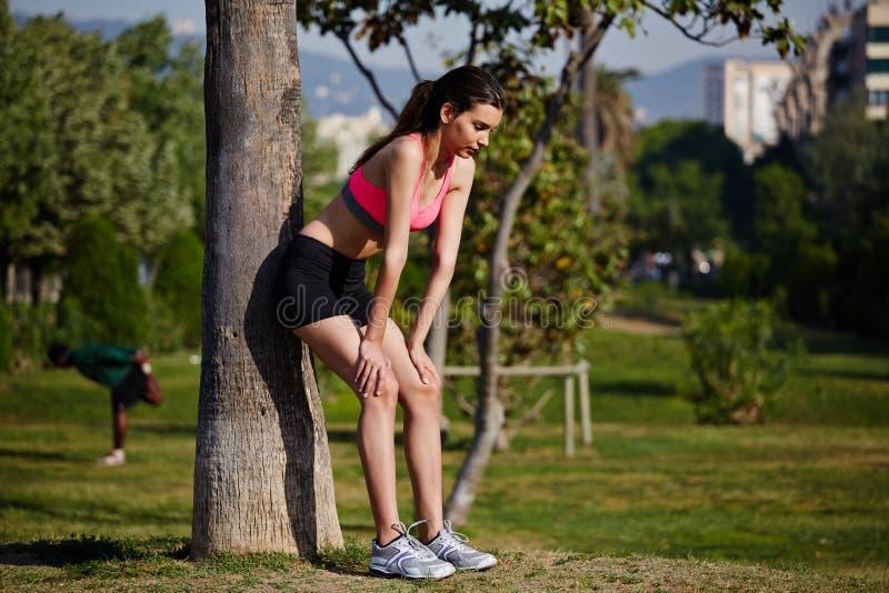 运动可爱的妇女倾斜了反对在跑步以后疲倦的树 免版税图库摄影