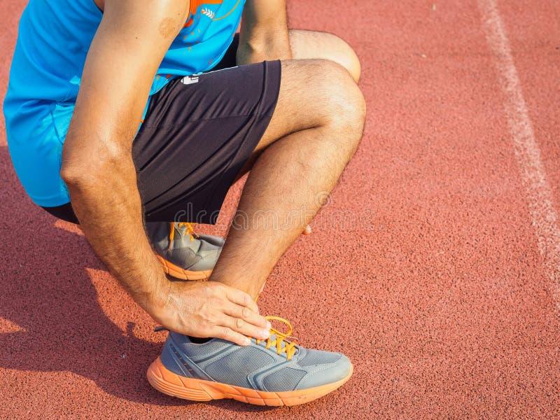 运动员人有脚踝受伤,在连续traini期间的被扭伤的腿 库存照片