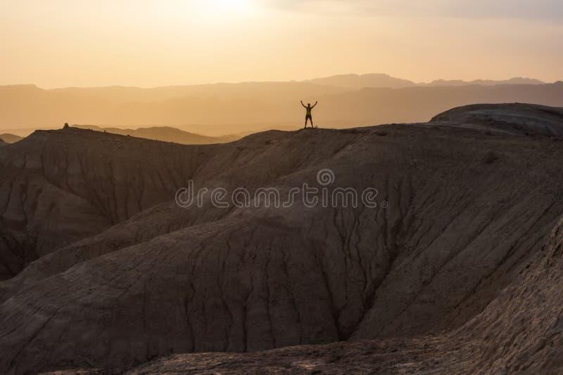 运动员人站立在小山顶部 胜利喜悦  在山的日落 免版税库存照片