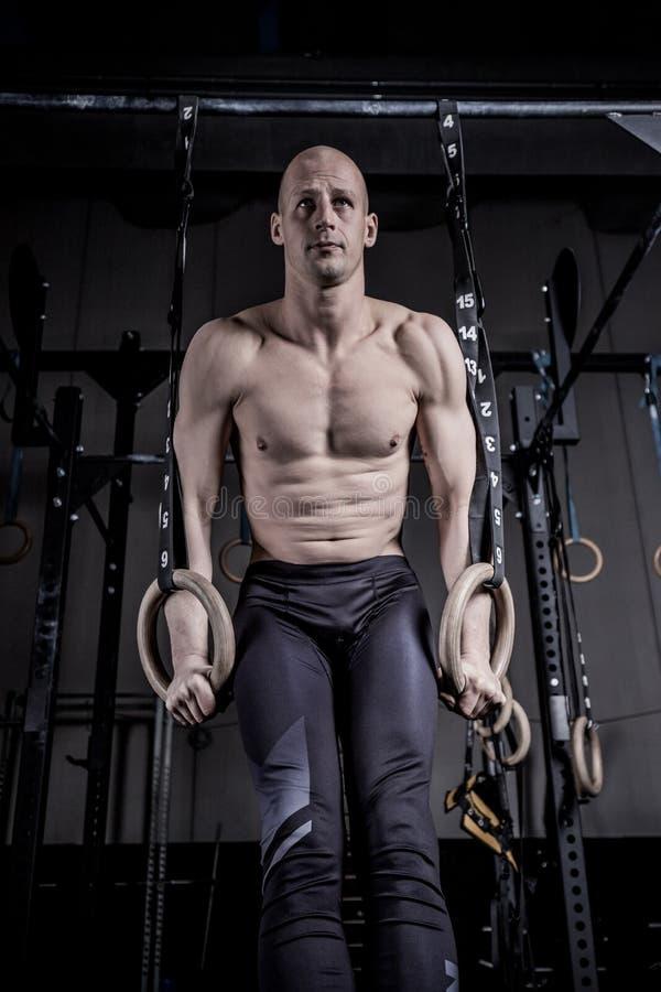 运动员做增加与圆环在健身房 免版税库存照片