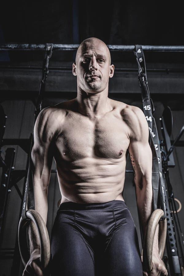 运动员做增加与圆环在健身房 库存照片