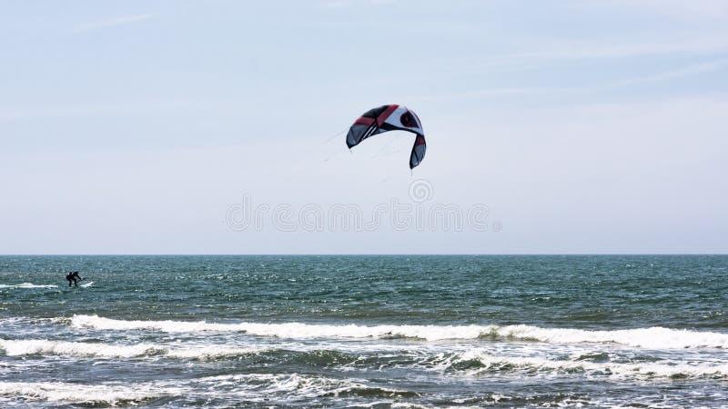 运动员在一理想的天与风大浪急的海面和完善的天气原因执行kitesurfing在波浪和泡沫之间对保证的乐趣 免版税库存图片