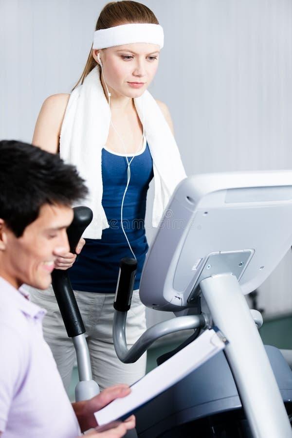 运动员在健身房设备的妇女训练在与教练的健身房 库存照片