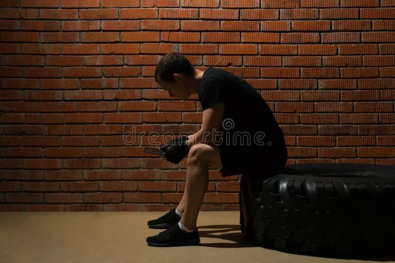 运动员在电话坐轮胎和看为锻炼计划反对砖墙背景 图库摄影