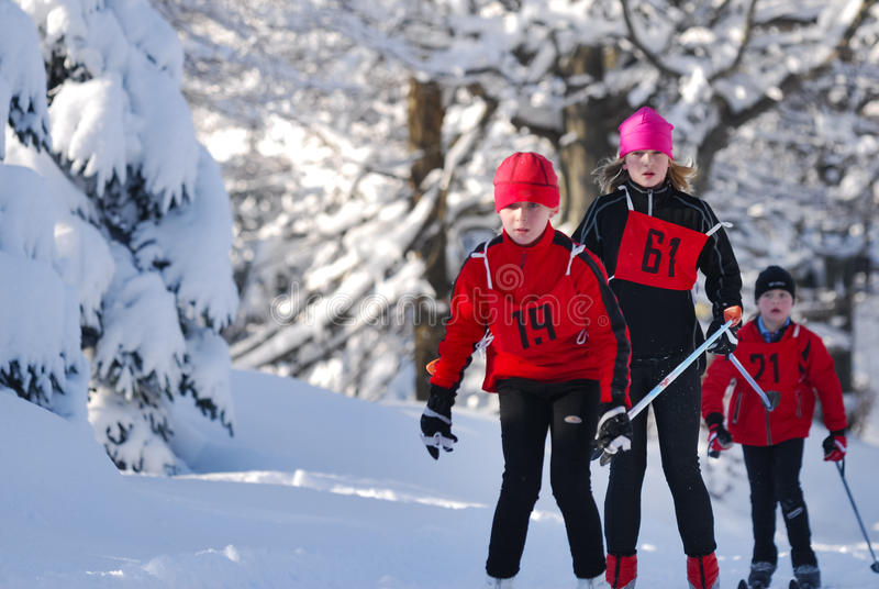 运动员在积雪的风景的孩子滑雪横越全国的连续冬天竞争中 库存图片