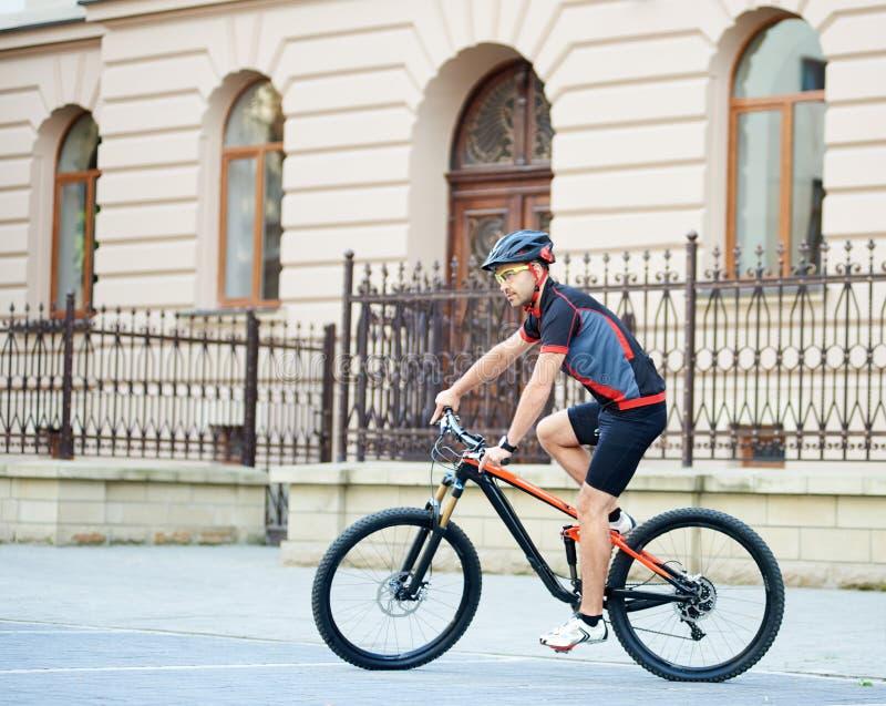 运动员在老大厦旁边的骑马自行车 免版税库存照片