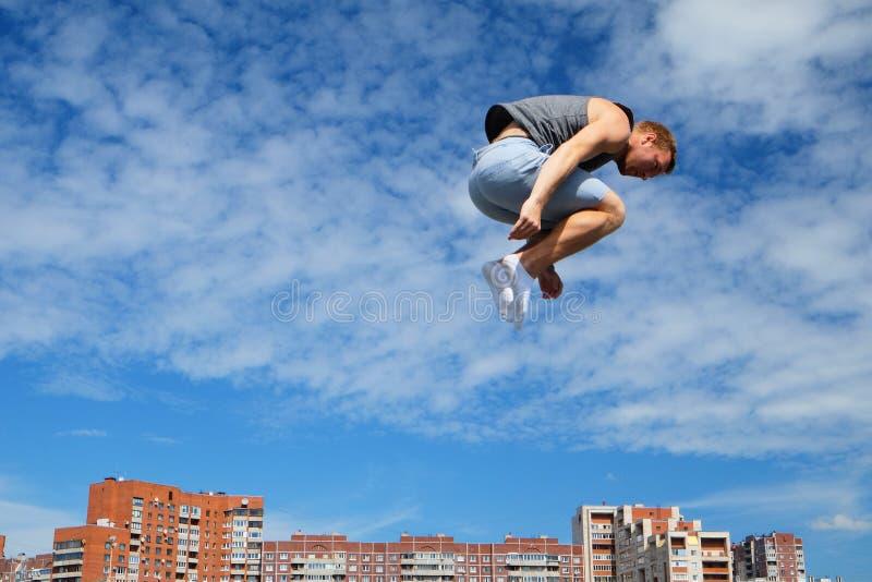 运动员在背景进行跳在绷床城市和天空的房子 库存照片