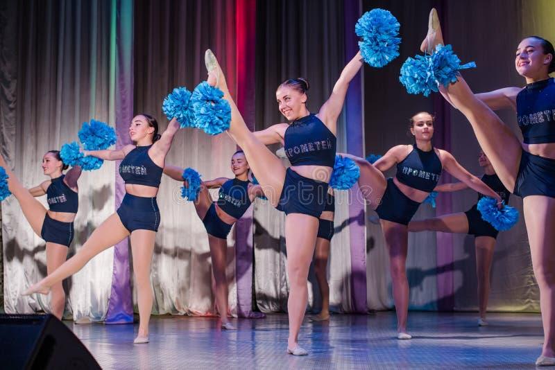 运动员在阶段执行,年轻啦啦队员执行在啦啦队欢呼的冠军,跃迁的女孩,女孩拿着绒球 库存照片