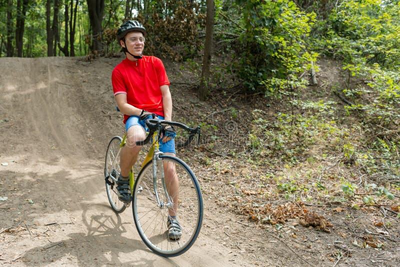 运动员坐自行车 佩带的体育适应,盔甲和玻璃 r 库存照片