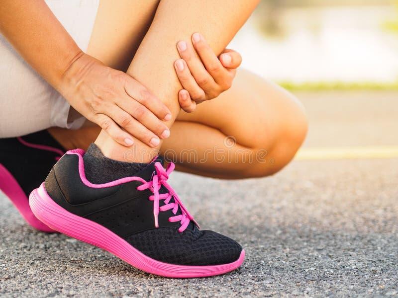 运动员妇女有脚踝受伤,在连续trai期间的被扭伤的腿 免版税图库摄影