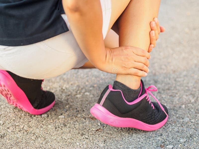 运动员妇女有脚踝受伤,在连续trai期间的被扭伤的腿 库存照片
