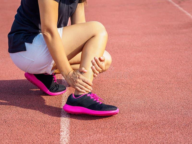 运动员妇女有脚踝受伤,在连续trai期间的被扭伤的腿 免版税库存照片