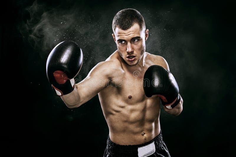 运动员战斗在拳击笼子的手套的泰拳拳击手 隔绝在与烟的黑背景 复制空间 库存图片