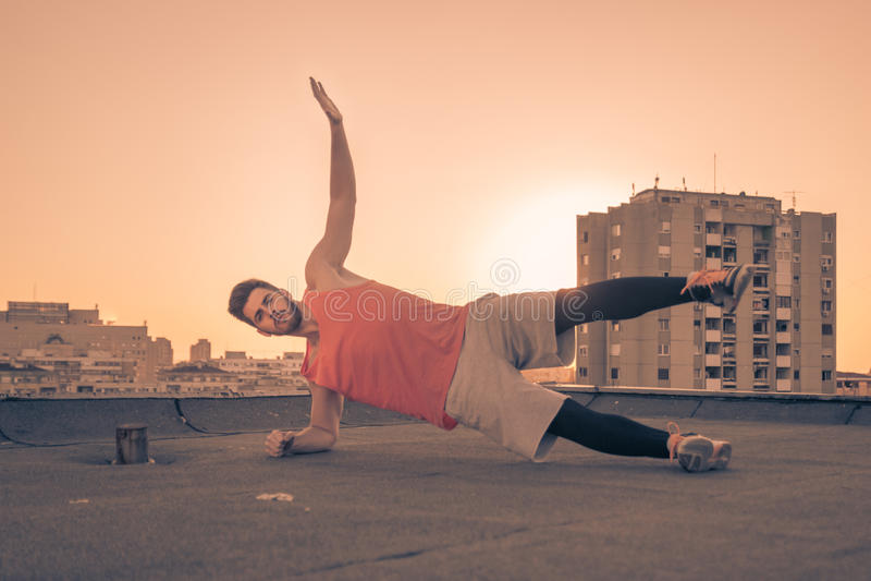 运动员旁边板条锻炼,太阳日落日出,屋顶屋顶 图库摄影