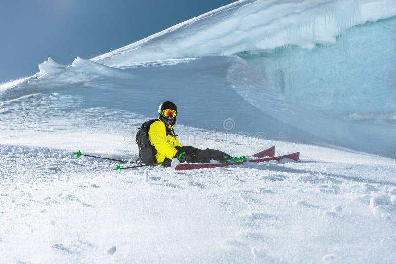 运动员滑雪者坐一个多雪的倾斜以冰墙壁为背景 专业滑雪 寒假 免版税库存图片