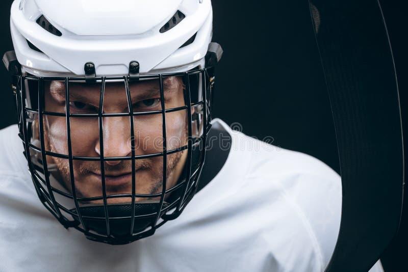 运动员画象曲棍球制服的在黑背景 免版税图库摄影