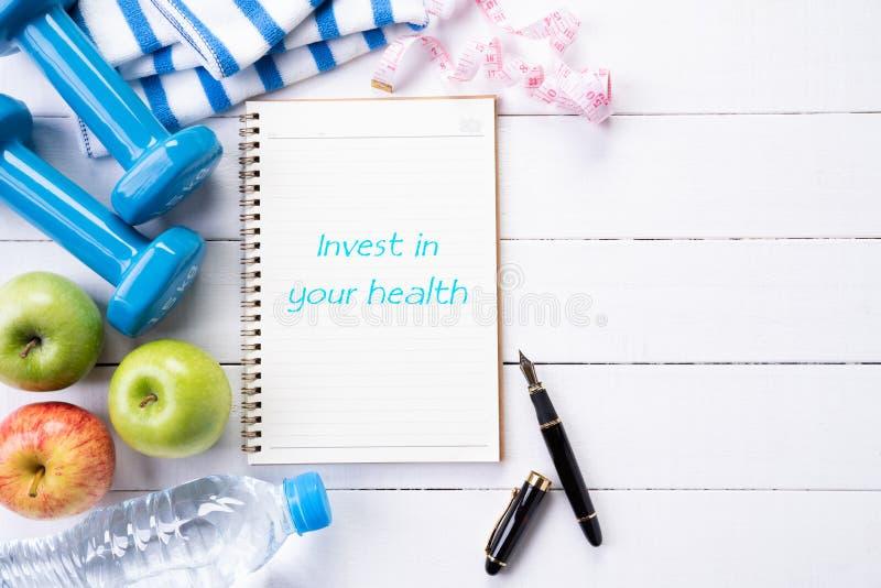 运动员的设备蓝色哑铃顶视图,体育水瓶、毛巾和笔记本与在您的在白色的健康文本投资 库存照片
