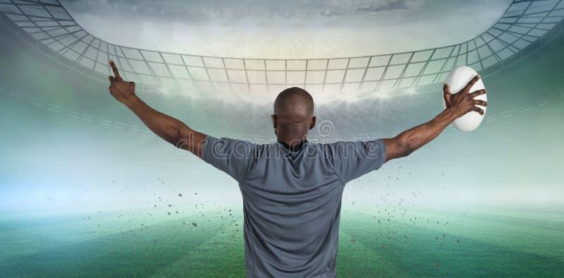 运动员背面图的综合图象有胳膊的提高了拿着橄榄球球 库存照片