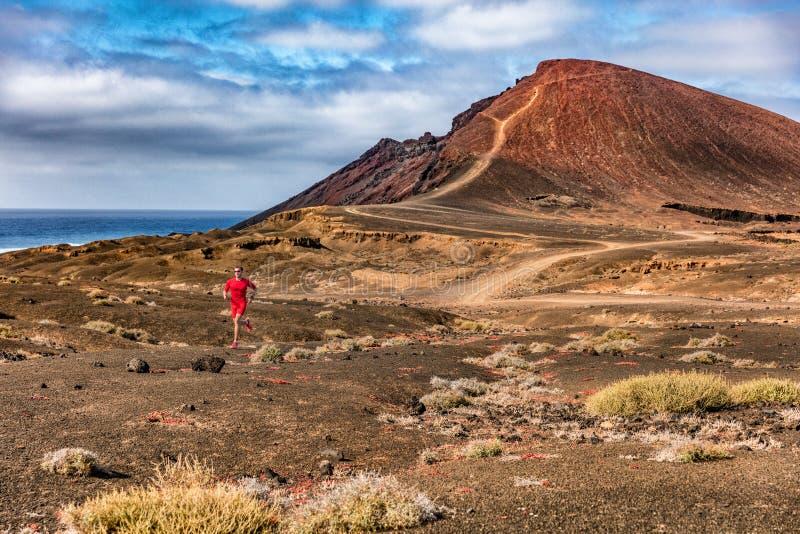 运动员赛跑者跑在火山的山背景地形的人足迹 体育和健身 在自然击中的英雄 库存图片