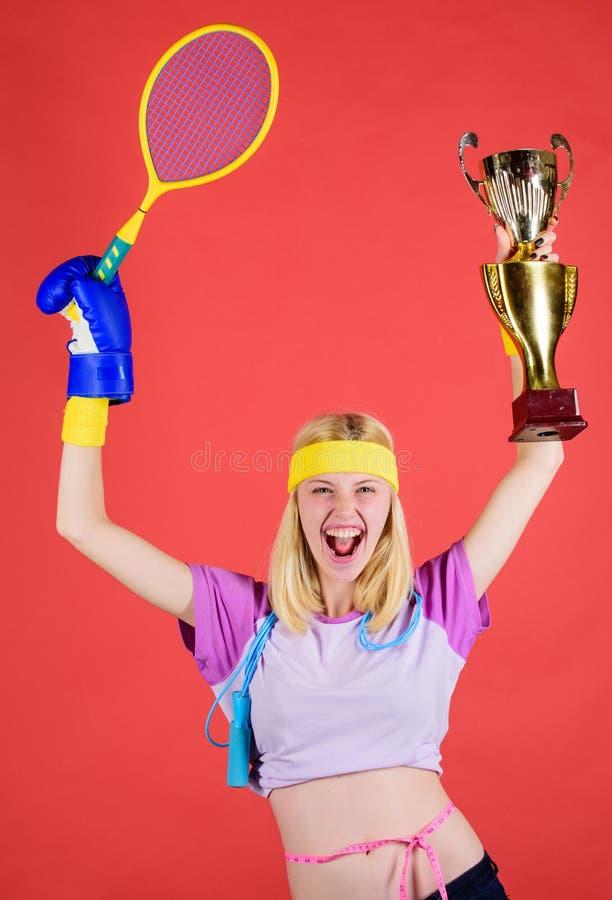 运动器材商店 体育商店分类 女孩快乐的成功的现代妇女举行金黄觚体育冠军 图库摄影