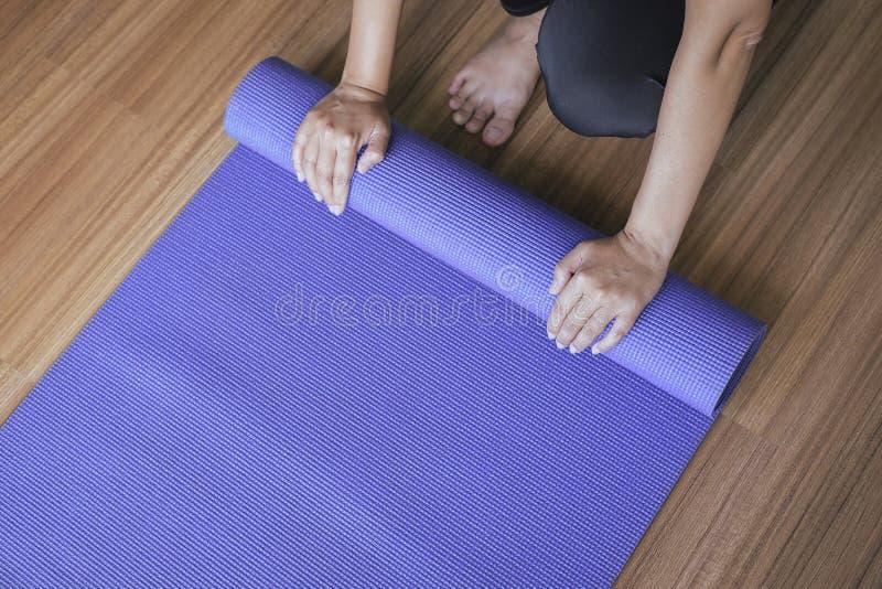 运动器材,妇女手辗压或折叠紫色在锻炼以后的瑜伽席子,健康健身和体育概念 免版税库存图片